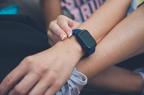 Person Wearing Blue and Black Smart Watch