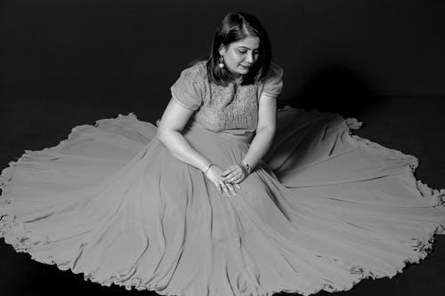 Woman Wearing a Dress Sitting on Black Surface