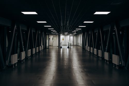 Spacious modern long corridor with clean floor with tile and luminous lamps in darkness