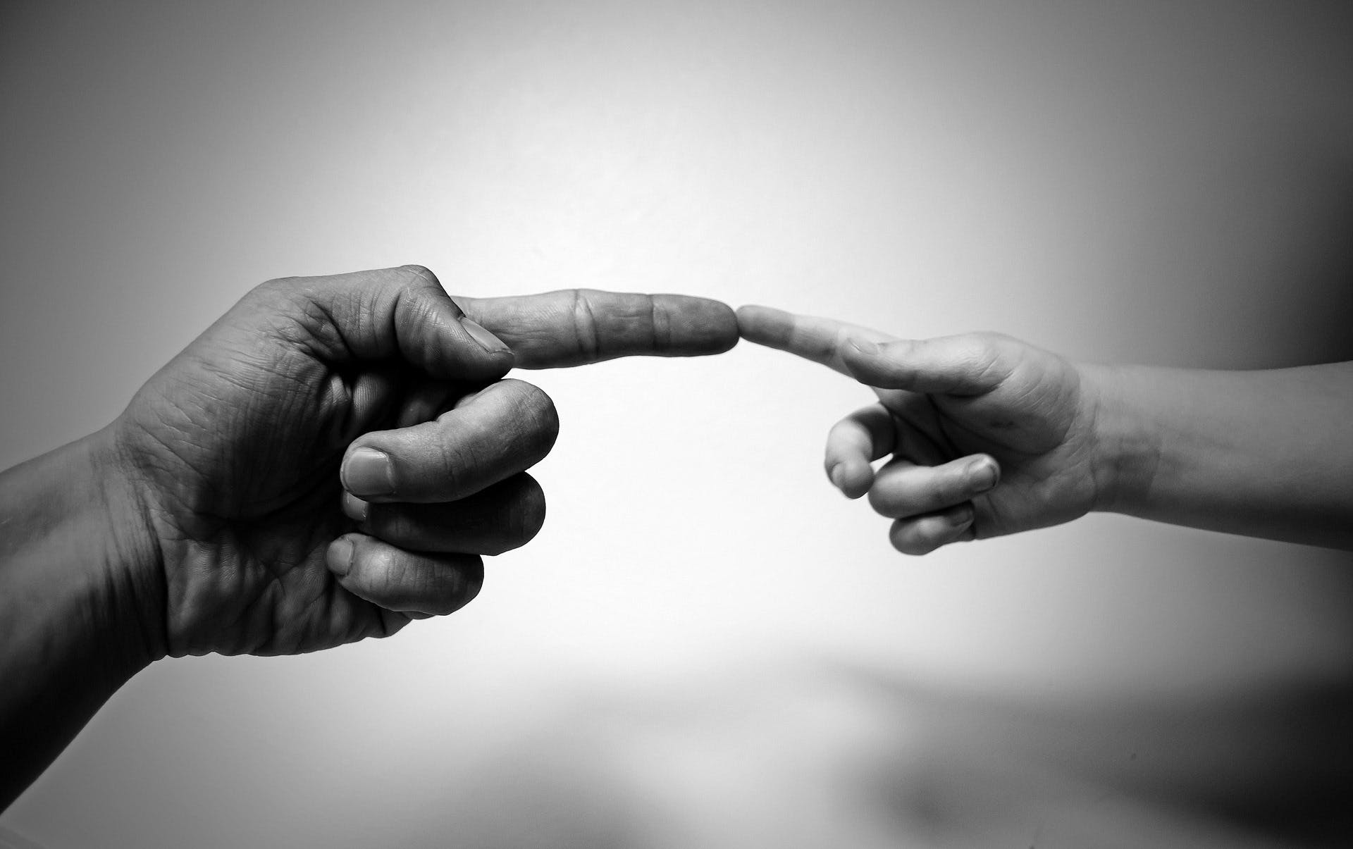 Grayscale Photo of Human Aligning Fingers
