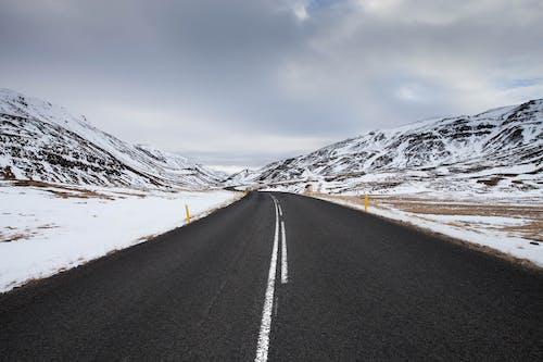 Black Asphalt Road Near Snow Covered Mountain Under Cloudy Sky