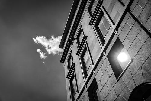 From below black and white of modern multistory building in daytime in sunny day