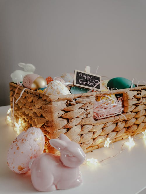 Close-Up Shot of Easter Eggs on a Basket beside an Easter Bunny Figurine