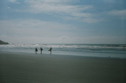 People Carrying Surfboards Walking on Beach