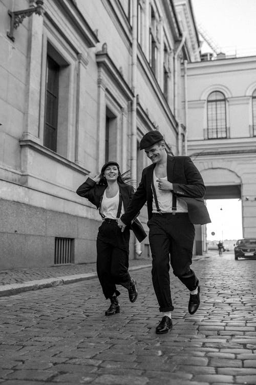 Grayscale Photo of a Happy Couple Holding Hands while Walking