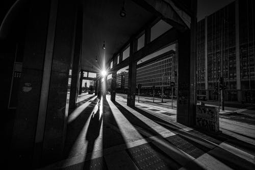 Black and white of anonymous silhouette of person walking along open passage of building
