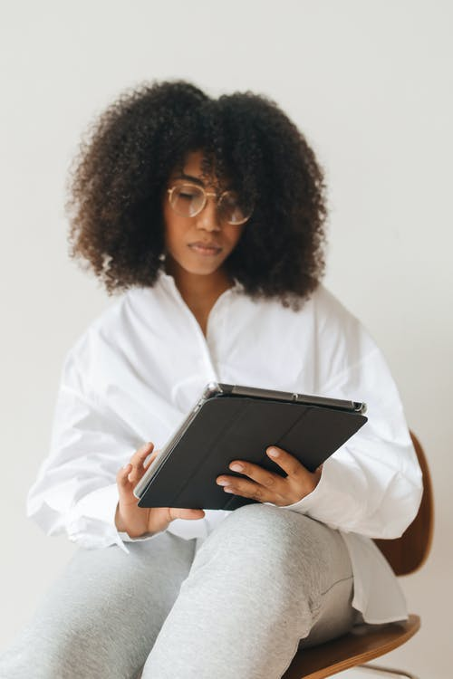 A Woman in a Dress Shirt Using a Tablet