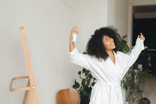 Woman in White Robe Holding White Hair Spray