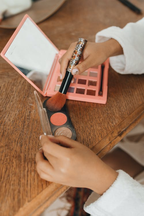 Woman Holding Makeup Brush and Pink Eyeshadow Palette