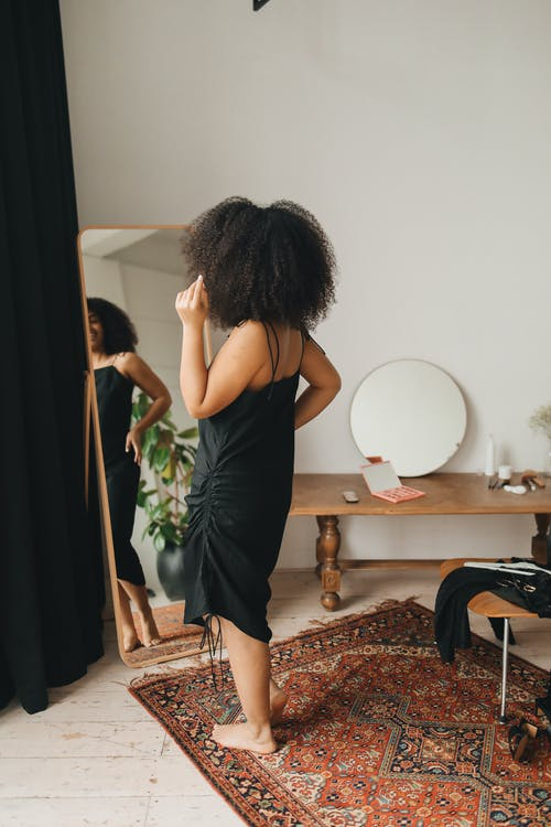 Woman in Black Dress Standing in front of the Mirror