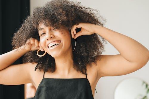 Woman in Black Dress Trying Gold Earrings