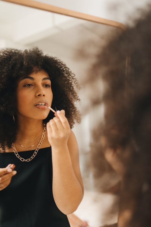 Woman in Black Dress Putting Lipstick