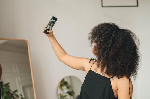 Woman in Black Spaghetti Strap Top Holding Smartphone