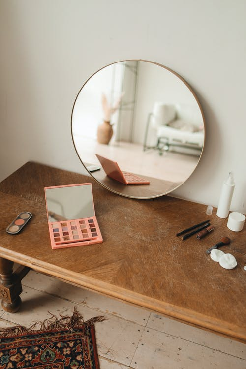 Round Mirror on Brown Wooden Table