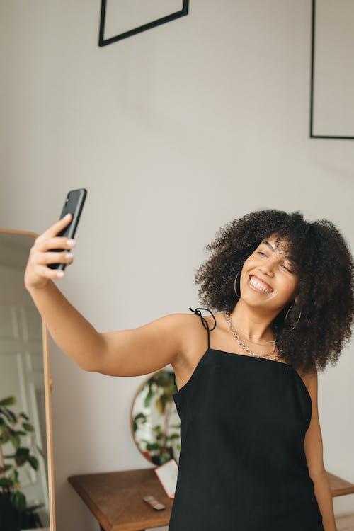 Woman Wearing Black Dress Taking a Selfie