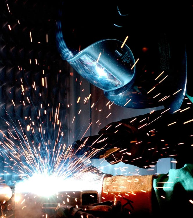 Person in Welding Mask While Welding a Metal Bar