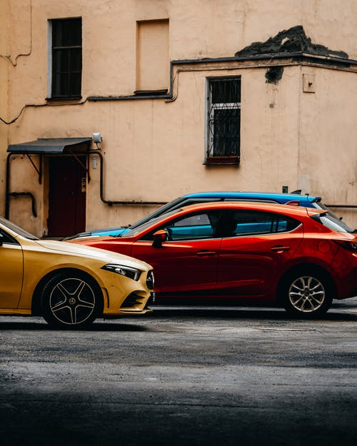 Red and Yellow Coupe Parked Beside Brown Concrete Building