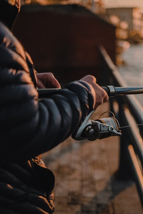 A Man in a Puffer Jacket Holding a Fishing Rod