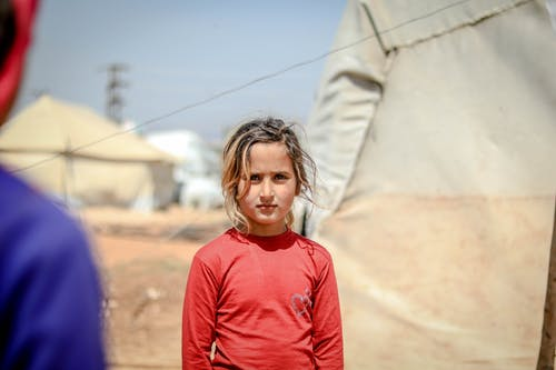 A Girl in Red Long Sleeves at a Refugee Camp