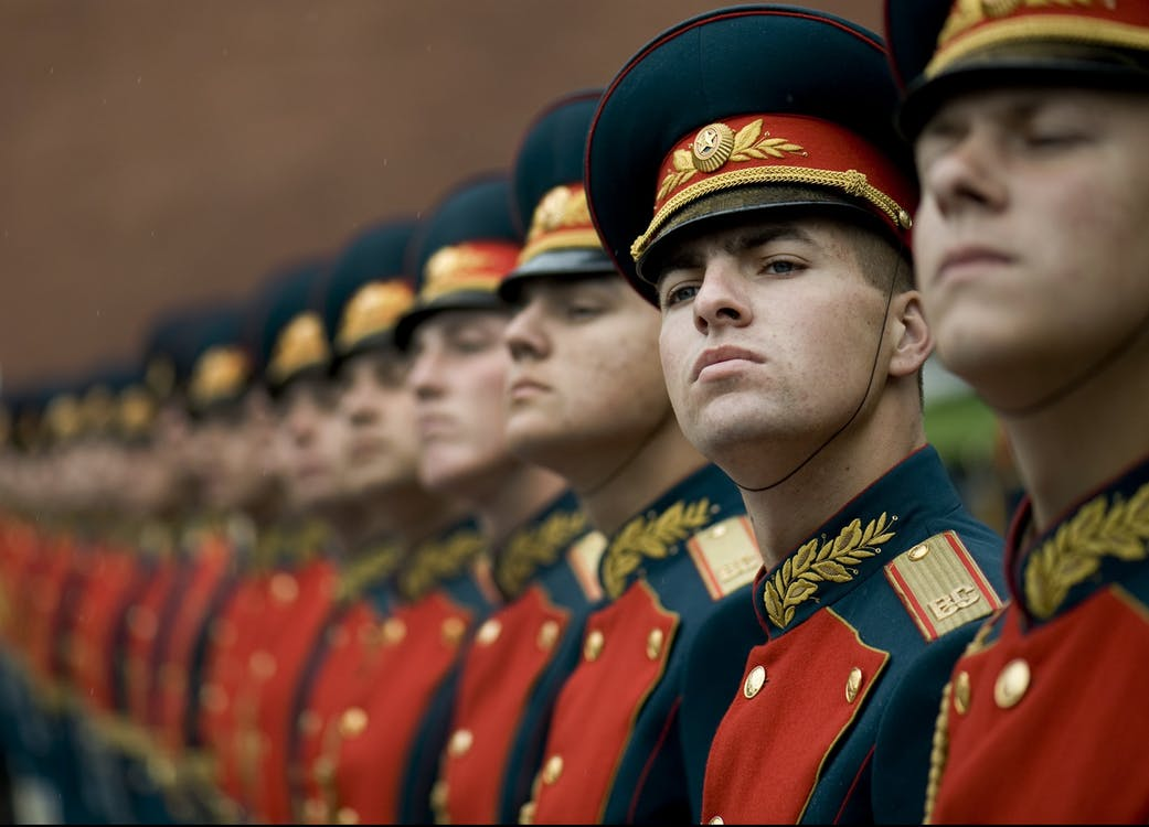 Men in Black and Red Cade Hats and Military Uniform