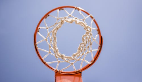 From below of metal basketball hoop with net hanging on sports ground against blue sky