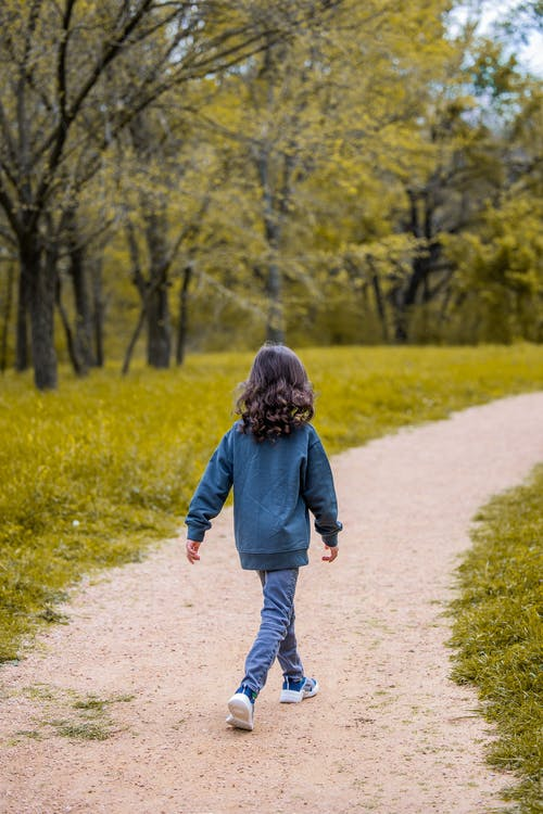 Unrecognizable girl walking on curved path in park