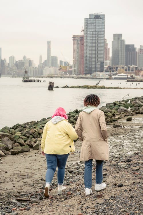 Back view full body of anonymous couple in outerwear strolling on waterside with stones near calm river against residential buildings