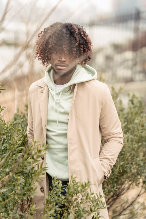 Serious black man standing near bush