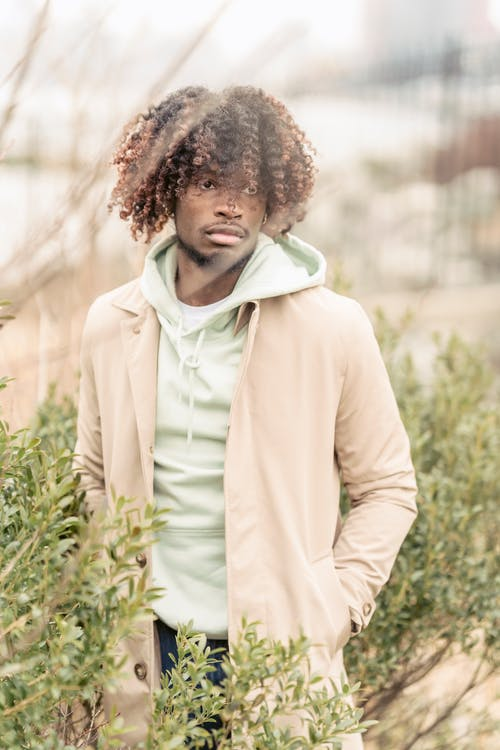 Serious African American male in stylish clothes looking away while standing on street with hand in pocket near lush shrubs on blurred background