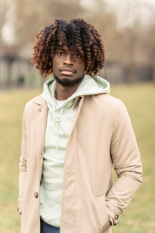Serious African American male in trendy coat looking away while standing with hand in pockets on grassy ground in park on blurred background