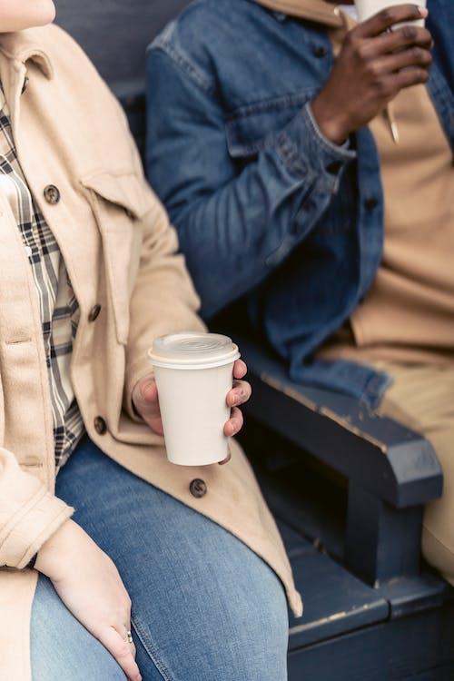 Anonymous woman drinking coffee near black man
