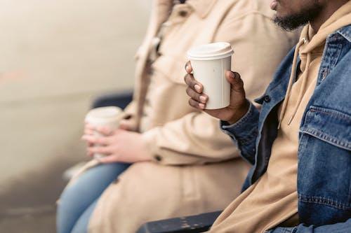 Black guy drinking coffee near girlfriend