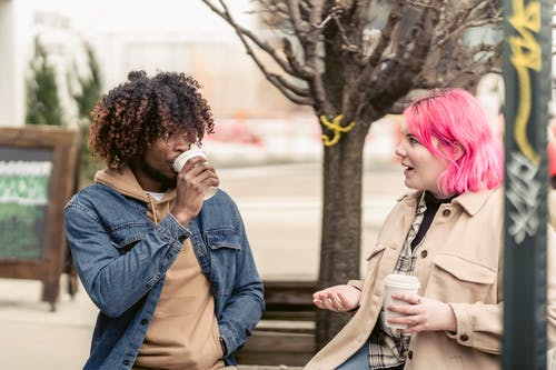 Trendy young informal female millennial with pink dyed hair in stylish outfit sitting on bench and chatting with African American male friend during coffee break in city park