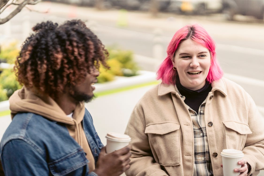 Cheerful young female teenager with dyed pink hair in stylish warm clothes smiling and drinking coffee to go while speaking with positive black male friend in park
