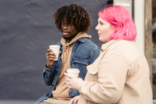 Trendy young African American guy with curly hair in stylish outfit drinking takeaway coffee and speaking with calm female friend while sitting together on bench on street
