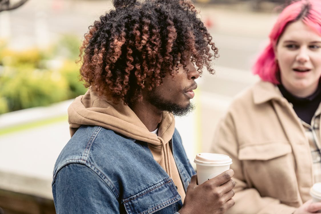 Stylish young multiethnic friends having coffee break in park