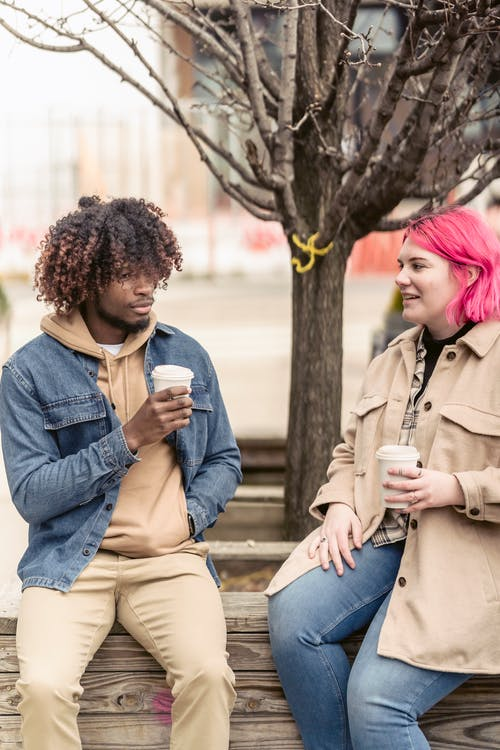 Multiethnic friends drinking coffee in park