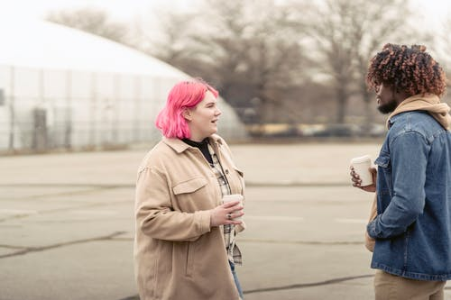 Plus size woman with pink hair enjoying coffee to go and talking with African American man while standing on city street on autumn day