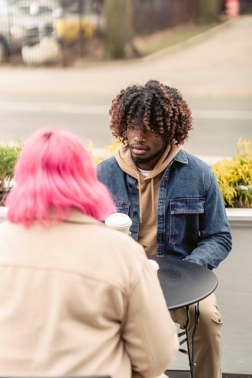 Black male listening to girlfriend in street cafe