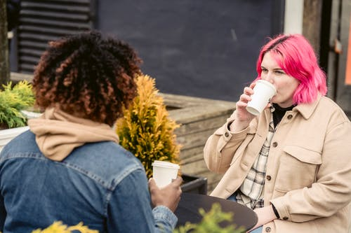 Young female sipping coffee to go while sitting at table and resting on weekend day in outdoor cafe