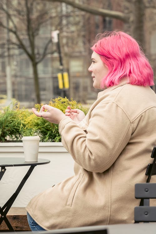 Woman with pink hair in street cafe