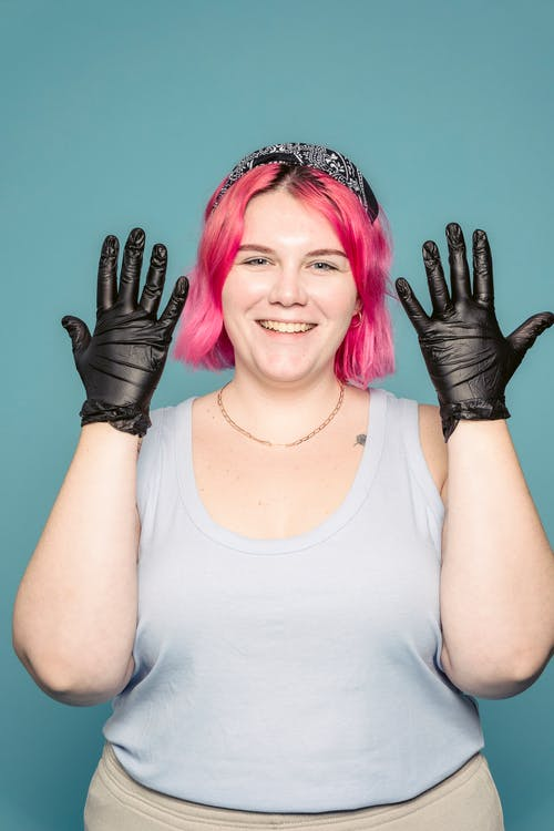 Happy female stylist showing gloves