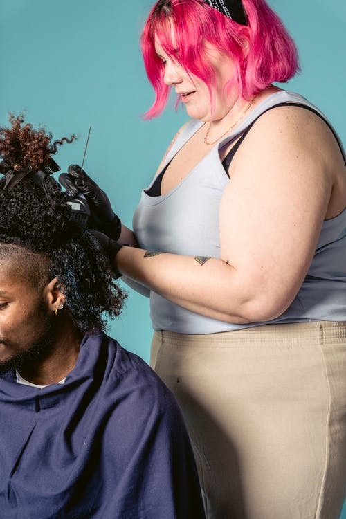 Side view of professional hairdresser in black gloves coloring hair with brush to African American male client against blue background