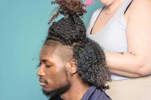 Black man sitting in hairdressing studio