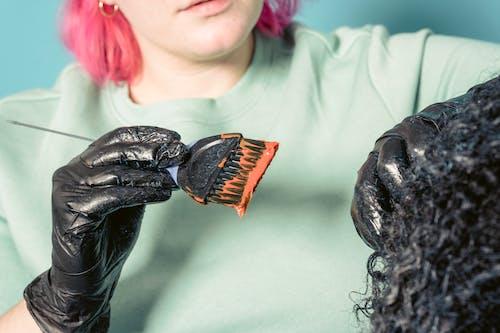 Hairdresser applying dye on head of customer