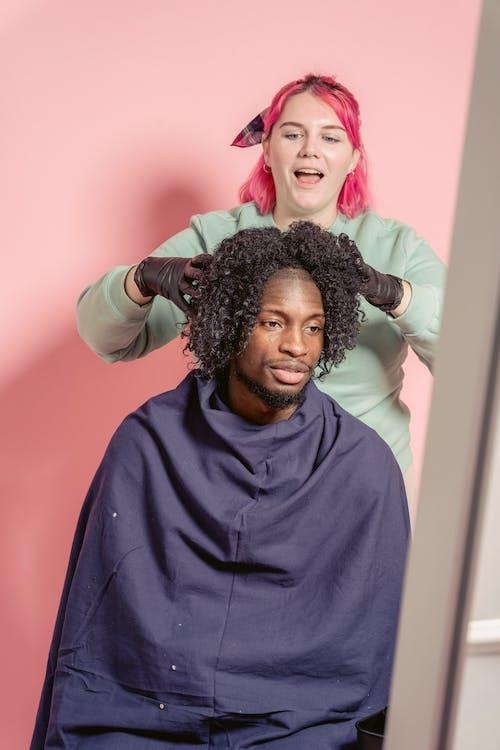 Woman touching hair of black customer in hairdressing studio