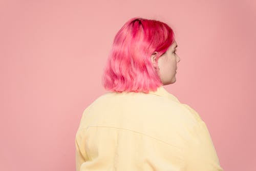 Back view of female model with bright dyed hair against pink background looking away