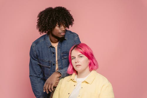 Young black man leaning on shoulder of woman with dyed hair sitting against pink background