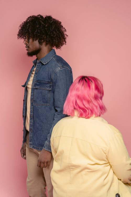 African American male in casual clothes standing near female with dyed hair while pink background