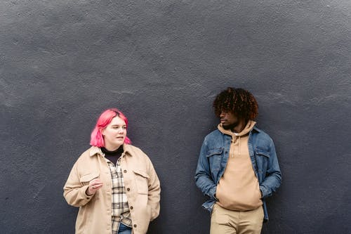 Calm multiracial couple in stylish clothes standing near concrete gray wall and talking in daytime
